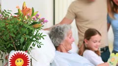 Smiling family standing together around a hospital bed - stock footage