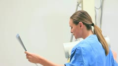 Smiling nurse holding x-ray while proceeding a radiography on a patient Stock Footage
