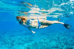 Woman snorkeling in tropical ocean Stock Photos