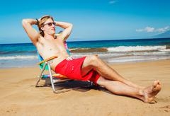 Stock Photo of young man relaxing at the beach