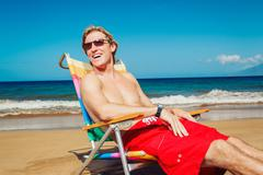 Young man relaxing at the beach Stock Photos