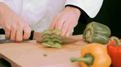 Woman cutting a green pepper in slow motion Stock Footage