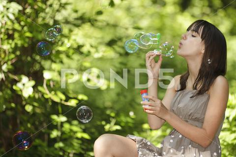 Stock photo of girl blowing bubbles