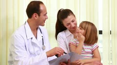 Doctor talking to a girl while she sits on the knees of her mother Stock Footage