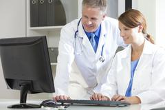 male female hospital doctors using computer - stock photo