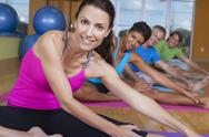 Stock Photo of interracial group of middle aged people practicing yoga
