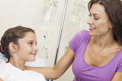 Stock Photo of mother visiting daughter child patient in hospital bed