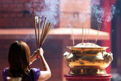 Woman holding incense sticks Stock Photos
