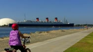 Father & Daughter Ride Bikes- Queen Mary In Background Stock Footage