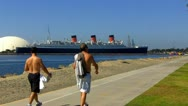 Father & Teen Son Walk With Queen Mary In Background Stock Footage