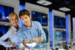 young couple in consumer electronics store - stock photo