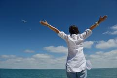 young woman with spreading arms to sky - stock photo