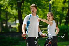 happy couple riding bicycle outdoors - stock photo