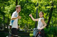 Happy couple riding bicycle outdoors Stock Photos