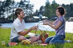 Stock Photo of happy young couple having a picnic outdoor