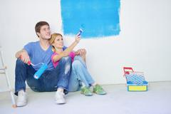 Stock Photo of happy young cople relaxing after painting in new home