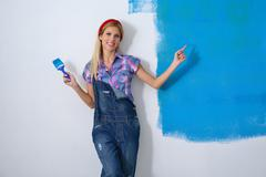 happy smiling woman painting interior of house - stock photo