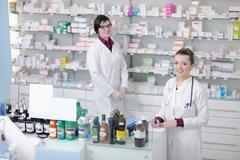 team of pharmacist chemist woman  in pharmacy drugstore - stock photo