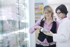 Pharmacist suggesting medical drug to buyer in pharmacy drugstore Stock Photos