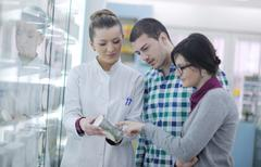 Pharmacist suggesting medical drug to buyer in pharmacy drugstore Stock Photos