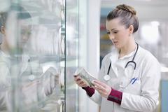 Stock Photo of pharmacist chemist woman standing in pharmacy drugstore