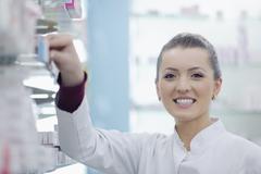 pharmacist chemist woman standing in pharmacy drugstore - stock photo