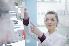 Pharmacist chemist woman standing in pharmacy drugstore Stock Photos