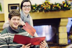 Young romantic couple sitting and relaxing in front of fireplace at home Stock Photos