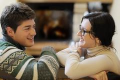 young romantic couple sitting and relaxing in front of fireplace at home - stock photo
