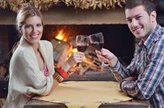 Stock Photo of young romantic couple sitting and relaxing in front of fireplace at home