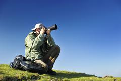 nature photographer with digital camera - stock photo