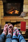 young romantic couple relax on sofa in front of fireplace at home - stock photo
