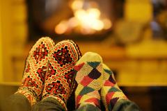 young romantic couple sitting on sofa in front of fireplace at home - stock photo