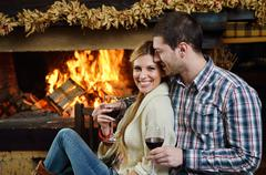 Stock Photo of young romantic couple sitting on sofa in front of fireplace at home