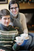 Young romantic couple sitting on sofa in front of fireplace at home Stock Photos