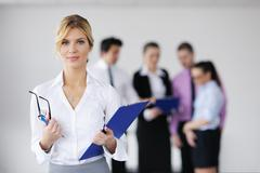 Business woman standing with her staff in background Stock Photos