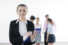 business woman standing with her staff in background - stock photo