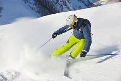 skiing on fresh snow at winter season at beautiful sunny day - stock photo