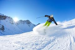 Skiing on fresh snow at winter season at beautiful sunny day Stock Photos