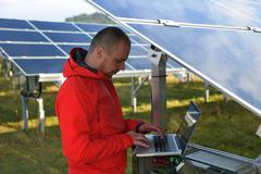 Stock Photo of engineer using laptop at solar panels plant field