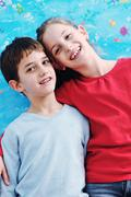 portrait of happy brother and sister at home - stock photo