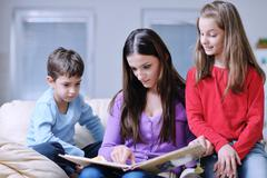 young mom play with their kids at home and reading book - stock photo
