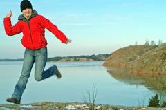Stock Photo of Young woman jumping, winter scene