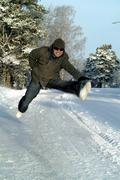 Young man jumping, winter scene Stock Photos