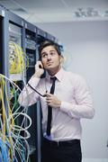 it engeneer talking by phone at network room - stock photo