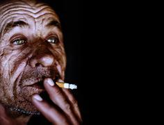 Stock Photo of Old wrinkled man smoking