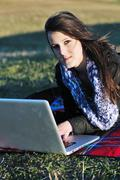 young teen girl work on laptop outdoor - stock photo