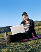 Young teen girl work on laptop outdoor Stock Photos