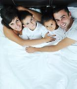 happy young family in their bedroom - stock photo