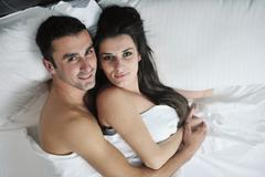 young couple have good time in their bedroom - stock photo